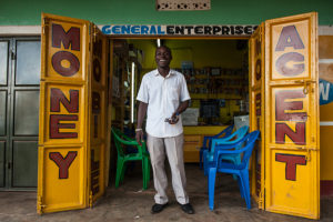 "MasterCard Foundation's partnership with Opportunity International and Opportunity Bank is expanding access to financial services to 1.4 million people, particularly in rural areas. Mobile phone banking is a large component of these activities. Julius Sakiaiiuu at his mobile phone shop and mobile money kiosk in Kanjuki Village. Julius received loans from Opportunity Bank to expand his mobile phone shop in Kanjuki Village. ""Before mobile banking, I would have to bay 10,000 shillings to go to the nearest bank branch to deposit 10,000 shillings,"" he said."